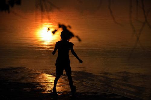 unbekanntes Kind spielt auf einem nassen Bootssteg im Sonnenuntergang